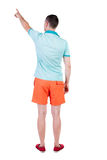Vista posteriore di indicare i giovani in maglietta e negli shorts Immagine Stock