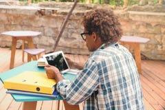 Vista posteriore di seduta africana concenrated dell'uomo e della compressa usando Immagini Stock Libere da Diritti
