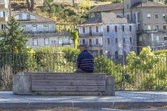 Vista posteriore di seduta di rilassamento dell'uomo senior su un banco concreto e di legno sul bordo pedonale di una strada del  fotografia stock