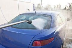 Vista posteriore di un'automobile nel carwash con il getto di acqua Fotografie Stock Libere da Diritti