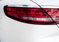 Vista posteriore e faro rosso dell'automobile bianca nel salone di vendite Immagine Stock Libera da Diritti