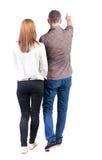 Vista posteriore indicare di giovane di camminata delle coppie (uomo e donna) Fotografia Stock