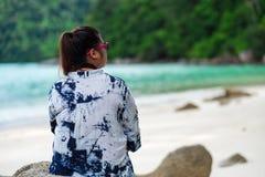 Vista posteriore occhiali da sole della donna dell'Asia e sittin d'uso della camicia dell'indaco Immagini Stock