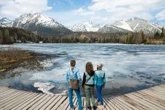 Vista posteriore su tre turisti femminili che restano dalla La congelata della montagna immagini stock libere da diritti