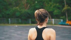 Vista posteriore sul giovane atleta Woman in attrezzatura di sport che cammina lungo gli sport Feld nel parco stock footage