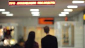 Vista posteriore Unfocused delle coppie che camminano giù il corridoio dell'aeroporto archivi video
