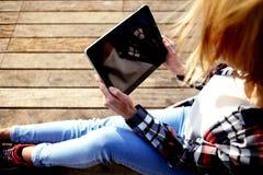Vista potata del colpo del cuscinetto di tocco della tenuta della ragazza dei pantaloni a vita bassa con lo schermo dello spazio  Fotografie Stock