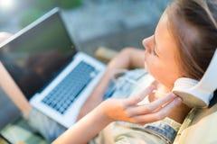 Vista potata del colpo di giovane introduzione teenager della ragazza sul compu del computer portatile Fotografia Stock