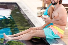 vista potata delle coppie che si rilassano vicino alla piscina fotografie stock