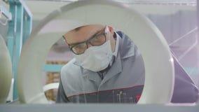A vista próxima através do empregado do furo da bobina verifica a qualidade da fibra de vidro vídeos de arquivo
