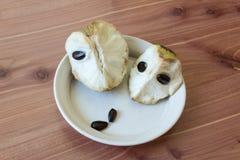 Vista próxima centrada de dois pedaços da annona cherimola do fruto da cherimólia em um prato raso com as sementes pretas numeros Fotografia de Stock Royalty Free