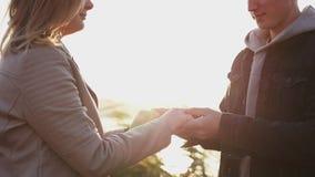 Vista próxima de em conjunto dos pares no amor no fundo do por do sol video estoque
