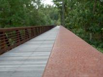 Vista próxima do trilho de mão oxidado ao longo de uma ponte de madeira do pé imagens de stock