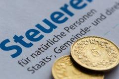 Vista próxima na declaração dourada suíça das moedas e de imposto de Zurique fotos de stock
