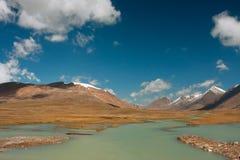 Vista preciosa de las montañas con las nubes en s azul Foto de archivo