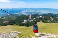 Vista rampicante della cabina di funivia dalla cima della montagna fotografie stock