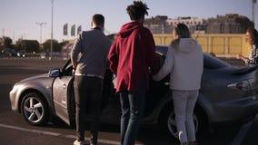 Vista rara pares jovenes de moda de un multirace de los dos que caminan por zona de aparcamiento de la alameda y sentarse en el c almacen de video