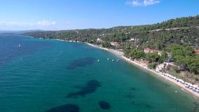 A vista a?rea da praia azul impressionante abaixo de um monte na ?rea de Halkidiki Gr?cia, abaixa para a frente e pelo zang?o filme