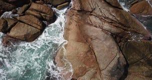 Vista a?rea de las ondas que se rompen en las piedras almacen de metraje de vídeo