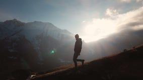 Vista a?rea de un tiro ?pico de un hombre que camina al borde de una monta?a como silueta en una puesta del sol hermosa Silueta almacen de video
