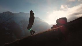 Vista a?rea de un tiro ?pico de un hombre que camina al borde de una monta?a como silueta en una puesta del sol hermosa Silueta metrajes