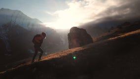 Vista a?rea do tiro ?pico de uma menina que anda na borda da montanha como uma silhueta em um por do sol bonito Silhueta filme