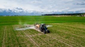 A vista a?rea, fazendeiro em um trator com um pulverizador faz o adubo para vegetais novos fotografia de stock royalty free