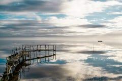 Vista relajante de un cielo azul reflejado con nubes, un muelle desvencijado y un barco de pesca. Fotos de archivo libres de regalías