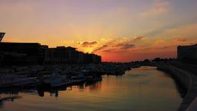 Vista relajante hermosa de los barcos y de las construcciones de viviendas modernas en la puesta del sol, Abu Dhabi Al Bateen del almacen de video