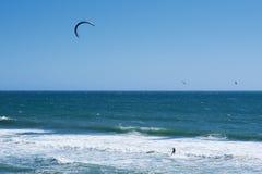 Vista remota nos surfistas do papagaio que montam as ondas Imagem de Stock