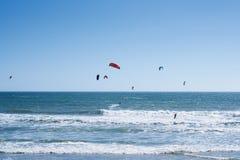 Vista remota nos surfistas do papagaio que montam as ondas Foto de Stock