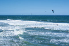 Vista remota nos surfistas do papagaio que montam as ondas Fotos de Stock Royalty Free