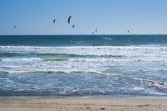 Vista remota nos surfistas do papagaio que montam as ondas Fotografia de Stock