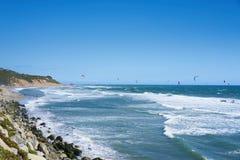 Vista remota nos surfistas do papagaio que montam as ondas Imagens de Stock