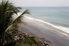 Vista romântica da praia com folhas de palmeira no primeiro plano Foto de Stock Royalty Free