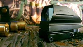 Vista rossa del punto di obiettivi, munizioni e bandoliera su un fondo del cammuffamento, carta da parati fotografia stock libera da diritti
