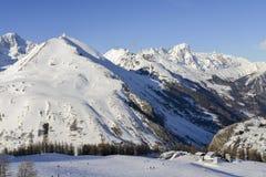 Vista sbalorditiva dei picchi di alta montagna nell'arco alpino italiano, in un giorno soleggiato ed in un lotto luminosi di neve Immagini Stock