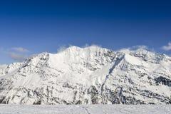 Vista sbalorditiva dei picchi di alta montagna nell'arco alpino italiano, in un giorno soleggiato ed in un lotto luminosi di neve Fotografia Stock Libera da Diritti