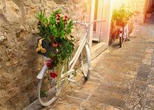 Vista sbalorditiva della via pavimentata lapidata in vecchia città su alba Vasi con i fiori che stanno sulle biciclette d'annata  Immagine Stock Libera da Diritti