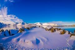 Vista scenica all'aperto con le rocce coperte di neve vicino ad un lago in Svolvaer Fotografia Stock Libera da Diritti