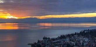 Vista scenica del tramonto sopra il lago Leman con il cielo giallo con le nuvole e le montagne delle alpi nel fondo, Montreux, Sv Fotografie Stock