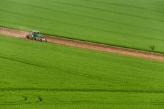 Vista scenica del trattore agricolo moderno che che ara campo verde Trattore di agricoltura che coltiva il giacimento di grano e  Fotografie Stock Libere da Diritti