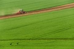 Vista scenica del trattore agricolo moderno che che ara campo verde Trattore di agricoltura che coltiva il giacimento di grano e  immagini stock