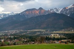 Vista scenica del villaggio di Koscielisko con panorama di alto Tatras su fondo, Polonia Immagini Stock Libere da Diritti