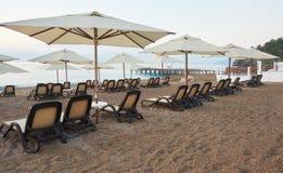 Vista scenica della spiaggia sabbiosa privata con i letti del sole dal mare e dalle montagne Amara Dols Vita Luxury Hotel ricorso immagine stock
