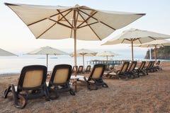 Vista scenica della spiaggia sabbiosa privata con i letti del sole dal mare e dalle montagne Amara Dols Vita Luxury Hotel ricorso immagine stock libera da diritti