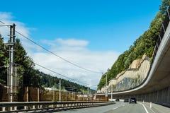 Vista scenica delle montagne delle alpi dell'incrocio di strada Fotografia Stock