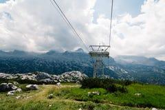 Vista scenica delle montagne delle alpi un il giorno soleggiato con la teleferica su foreg Fotografia Stock Libera da Diritti