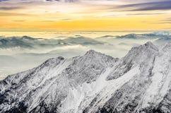 Vista scenica delle montagne nebbiose di inverno con il tramonto variopinto Fotografie Stock Libere da Diritti