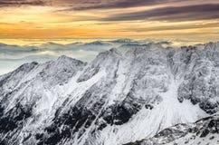 Vista scenica delle montagne nevose di inverno con il tramonto variopinto Immagine Stock